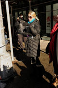 Naomi Watts stepping around mounds of snow in New York
